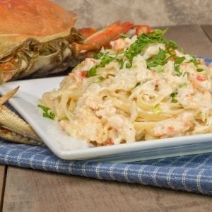 Dungeness,Crab,Pasta,Alfredo,On,A,White,Plate,With,Parsley